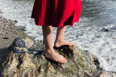 Feet of young woman standing on the beach Royalty Free Stock Image