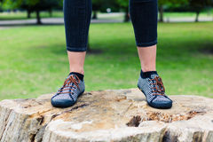 Feet of young woman standing on tree trunk Royalty Free Stock Photo