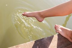 Feet of a young woman touching testing water. Closeup of sportive female legs, which are swinging, while touching water in a lake in a relaxed way. The young Stock Photos