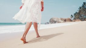 Feet of a young woman walking along an ocean beach on a sunny day. Slow motion stock footage