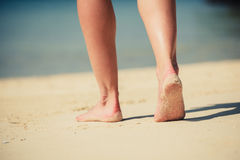 Feet of a young woman walking on the beach. The feet of a young woman as she is walking on the beach stock photography