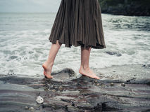 Feet of young woman walking on rocks in water Stock Photos