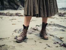 Feet of young woman wearing boots on beach Stock Photo