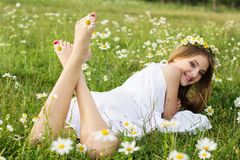 Feets of child girl with chamomiles Stock Images
