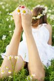 Feets of child girl with chamomiles Royalty Free Stock Photo