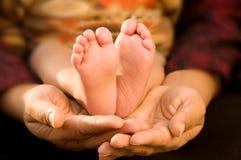 Feets del bebé en las manos de su madre Foto de archivo