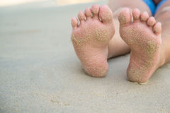 Feets with sand of lady sit on the beach Stock Photography