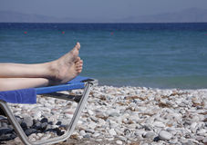 Feets on sunchair. Woman feets laying on sunchair focus on feets Stock Photography