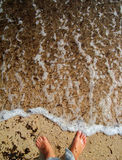 Feets on water. Feets on a coast line in transparen water Royalty Free Stock Image