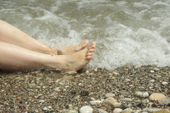 Feets in white caps. Woman feets laying in a sea water white caps Stock Photography