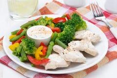 Feg filé, ångade grönsaker och yoghurtsås på en platta Arkivfoto