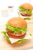 Feg hamburgare med grönsaker, ost på ett träbräde Arkivbilder