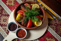 Feg kotlett med grönsaker i en lerakruka på ett ljust trämagasin, på en trätabell med en bordduk med nationella modeller arkivbilder