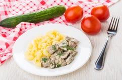 Feg lever med pasta i plattan, gurka, tomater, servett, f royaltyfri foto