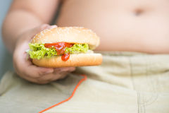 Feg osthamburgare på den sjukligt feta feta pojkehanden Royaltyfri Fotografi