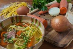 Feg soppa med nudlar på den lantliga trätabellen Arkivfoton
