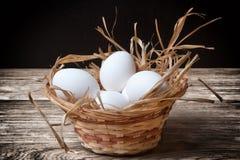 Fega ägg för vit i en vide- korg Arkivfoton