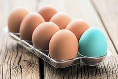 Fega ägg i en äggask på trätabellen royaltyfria foton