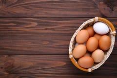 Fega ägg i korg på brun träbakgrund arkivbilder