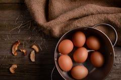 Fega ägg i panna på lantlig träbakgrund med säckvävsugrör Royaltyfri Fotografi