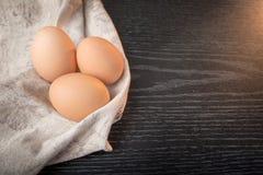 Fega bruna ägg i säckväv på trä backgroundChicken bruna ägg i säckväv på träbakgrund Arkivbilder