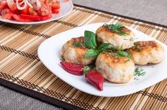 Fega köttbullar av köttfärs och en sallad av rå tomater royaltyfri foto