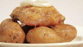 Fega lår med potatisar i deras hudar på en platta stock video
