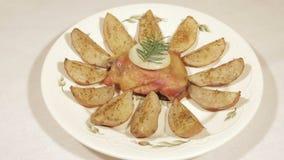 Fega lår med potatisar på en platta arkivfilmer