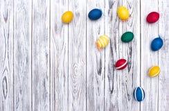 Fega mång--färgade påskägg på en vit träbakgrund, tradition, kopieringsutrymme, garnering, Maj arkivbilder
