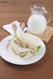 Fega smörgåsar på den vita maträtten med mjölkar och den trägaffeln och skeden royaltyfri fotografi