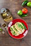 Fega taco för mexicansk mat med ingredienser och TequilaskottWi Arkivbilder