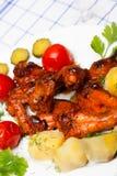 Fega vingar grillade med kokta potatisar och gravade tomater Royaltyfri Fotografi