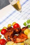 Fega vingar grillade med kokta potatisar och marinerade tomater Royaltyfri Fotografi