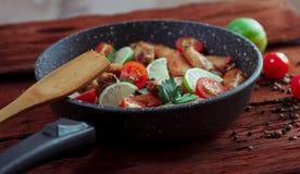 Fega vingar i pannan med tomater, limefrukt, persilja arkivfoto