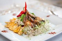Fega vingar, potatisar och grönsaker på en platta Arkivbilder