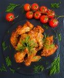 Fega vingar som lagas mat med grillfestsås på svart stenbakgrund Liten körsbärsröda tomater och dill Top beskådar Arkivbilder