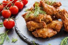 Fega vingar som lagas mat med grillfestsås på svart stenbakgrund Liten körsbärsröda tomater och dill Royaltyfria Foton