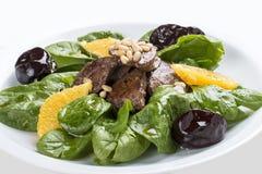 Fegato del manzo con spinaci e le prugne Su un piatto bianco immagini stock