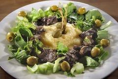 Fegato di pollo con la polenta, i caperberries, le erbe e le olive Fotografie Stock