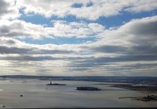 Fegende Vogelperspektive von New- Yorkhafen mit Freiheitsstatuen und Ellis Island im Abstand, mit cloudscape stockfotografie