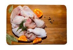 Fegt kött för råolja på en närliggande köksbord-, grönsak- och köktillbehörlögn royaltyfria foton
