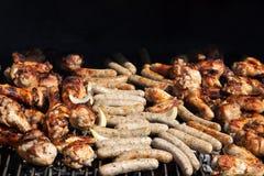 Fegt kött och korvar över kolen på en grillfest Begrepp arkivbild