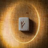 Fehu. Handmade scandinavian wooden runes on a wooden vintage background in a circle of light. Concept of fortune royalty free stock image