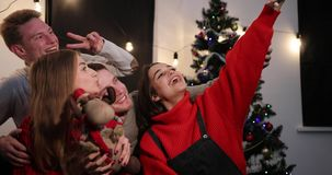 Feier des neuen Jahres Abnehmer mit zwei junger Paaren ein selfie auf dem Smartphone, der vor einem Weihnachtsbaum sitzt stock footage