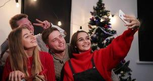 Feier des neuen Jahres Abnehmer mit zwei junger Paaren ein selfie auf dem Smartphone, der vor einem Weihnachtsbaum sitzt stock video footage