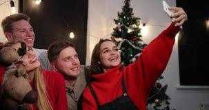 Feier des neuen Jahres Abnehmer mit zwei junger Paaren ein selfie auf dem Smartphone, der vor einem Weihnachtsbaum sitzt stock video