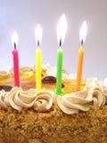 Feierliche Tabelle (Geburtstagkuchen und farbige Kerzen) Stockbild