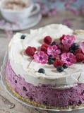 Feierlicher Kuchen mit Beeren und einer Schale aromatischem Kaffee Weinleseserviette, L?ffel und rosa Blumen lizenzfreies stockfoto