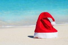 Feierlicher roter Santa Claus-Hut auf Strandhintergrund Stockfoto