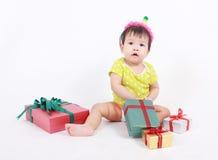 Feiern lachender tragender Parteihut des Babys, kleines Baby mit Haufen von Geschenkboxen Lizenzfreies Stockfoto